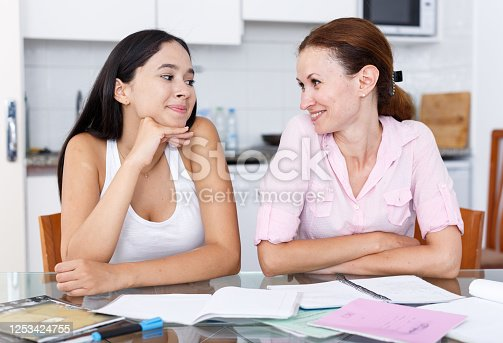 Mother rejoicing that her daughter is doing well in school in kitchen interior