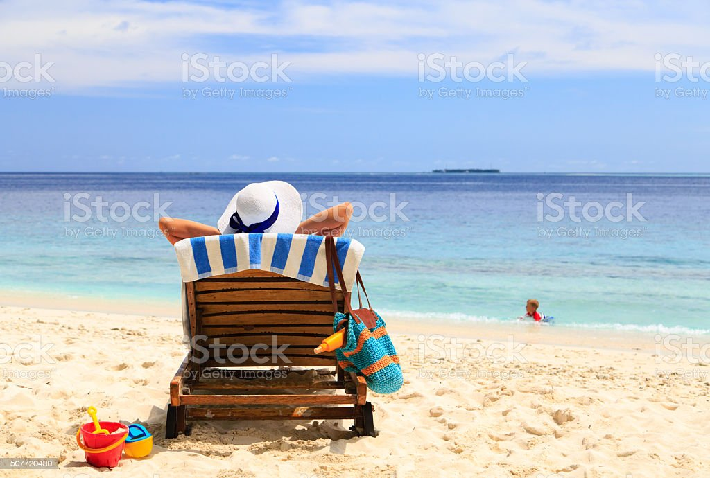 mother relax while kid play in water at the beach stock photo