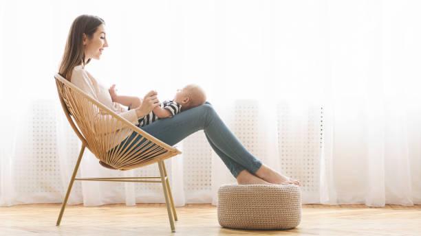 Mother relaxing in chair with her newborn baby on laps picture id1184182256?b=1&k=6&m=1184182256&s=612x612&w=0&h=mj2qdmffhxniumjrbboecjkky0v1y15kvznnrj0gtko=