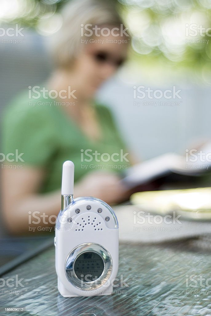 Mother resting with baby monitor by her side. stock photo