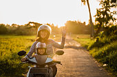 portrait of happy mother raise her arm while riding motorcycle with her daughter