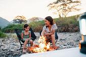 キャンプファイヤーで娘のためにマシュマロを焙煎する母