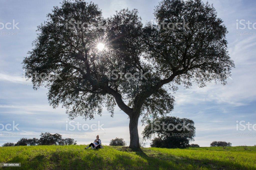 Madre mecer a un niño en brazos bajo árbol de bellota - foto de stock