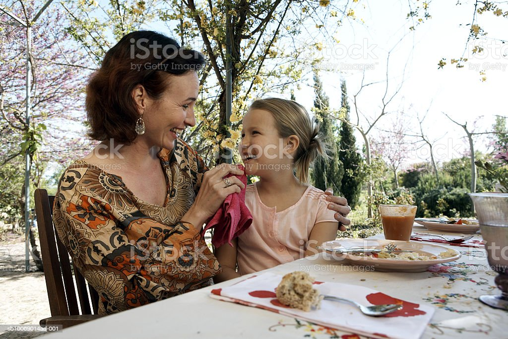 Mother rubbing daughter's (8-9) face at outdoor dining table royalty-free stock photo