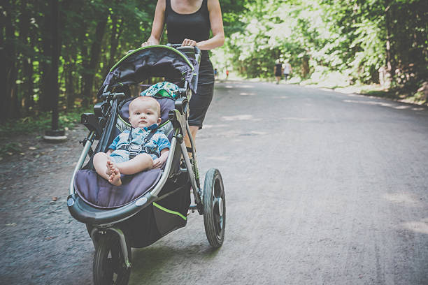 Mother Running Walking With baby Stroller in Park stock photo