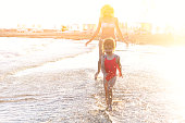 Happy family at the beach. Mother running with her baby daughter in sunset