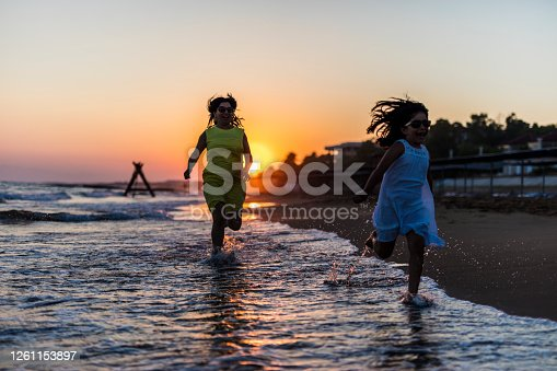 Mother running with her little daughter on the beach at sunset