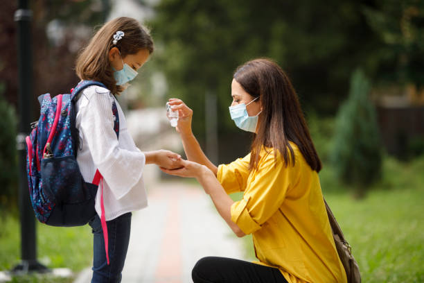Mother sanitizing her daughter's hands with antibacterial hand spray in front of the school stock photo