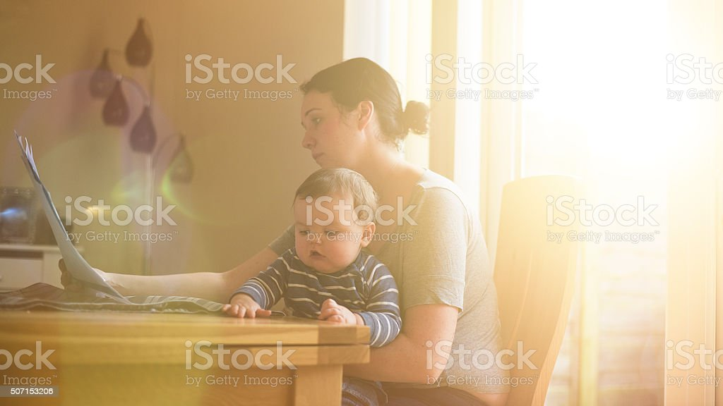 Mother sat with child worrying about her finances stock photo