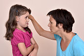 Angry mother scolding and pulling the ear of the scared daughter
