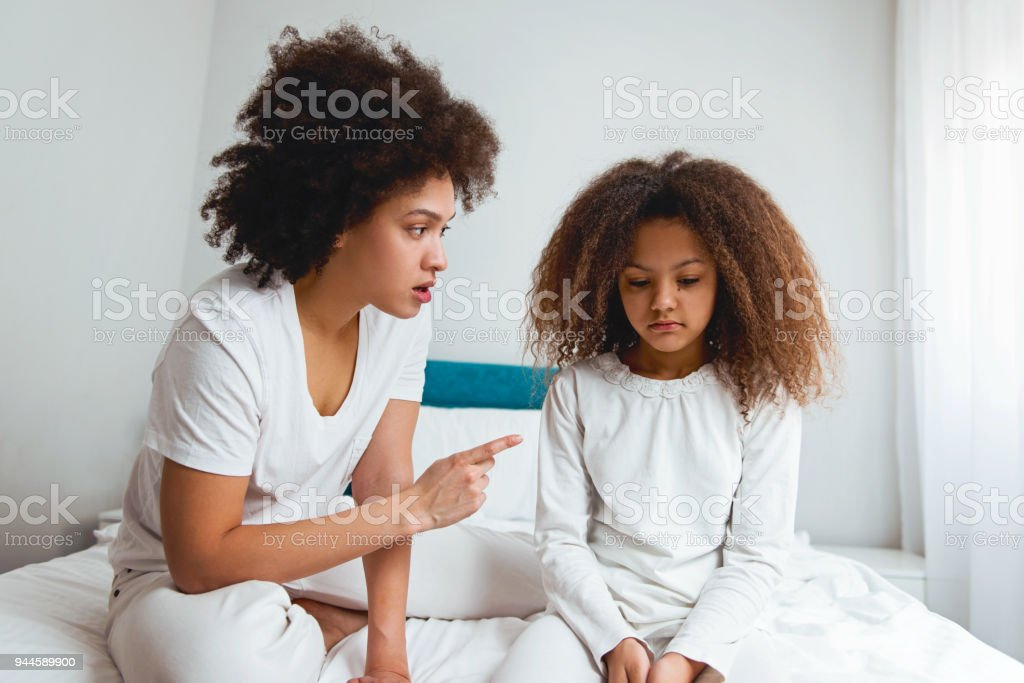 Mutter schelten ihre Tochter sitzen im Schlafzimmer – Foto