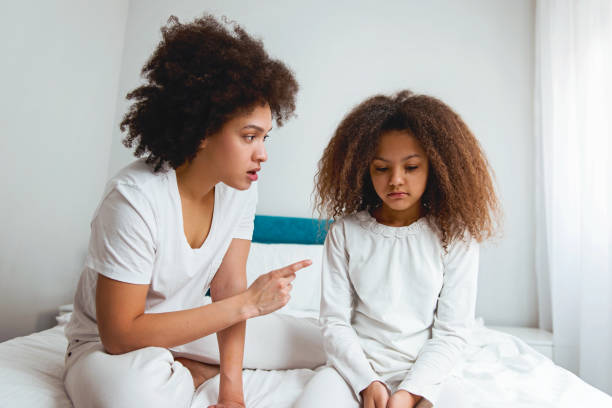 Mother scolding her daughter, sitting in the bedroom stock photo