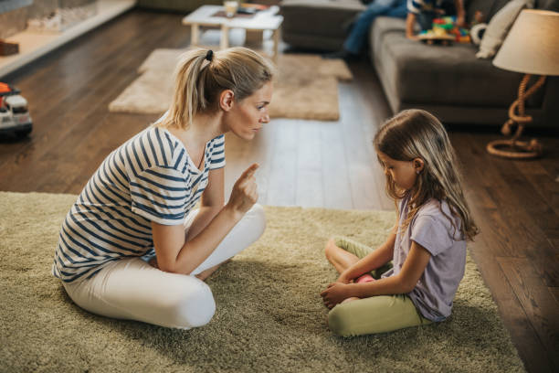 Mother scolding little girl on carpet in the living room. Young mother scolding her sad little daughter who made a mistake. scolding stock pictures, royalty-free photos & images