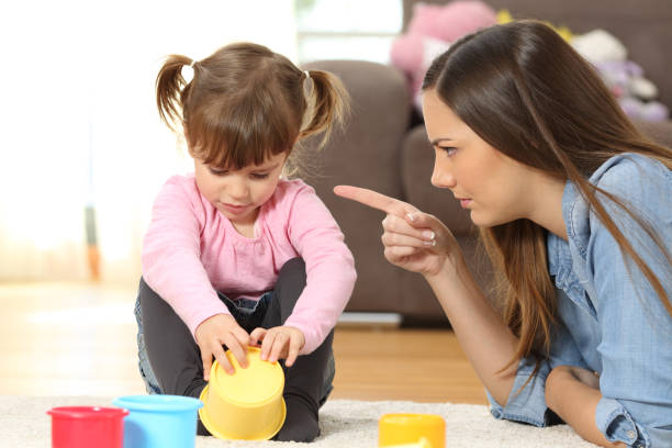 Mother scolding to her baby daughter Portrait of a mother scolding to her baby daughter sitting on the floor in the living room at home scolding stock pictures, royalty-free photos & images
