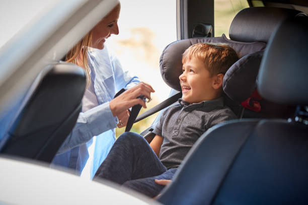 Mother Securing Son Into Rear Child Seat Before Car Journey stock photo