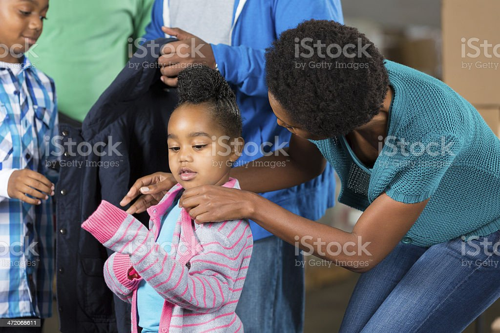 Mother selecting donated clothing for young daughter at community closet stock photo