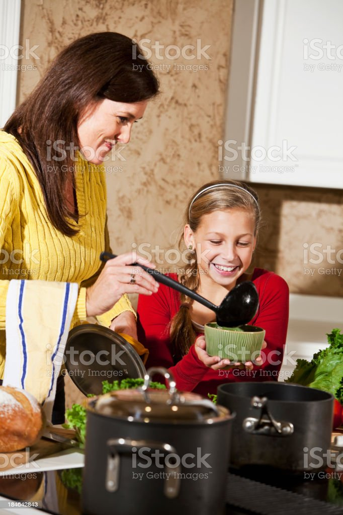 Mother serving daughter soup in kitchen royalty-free stock photo