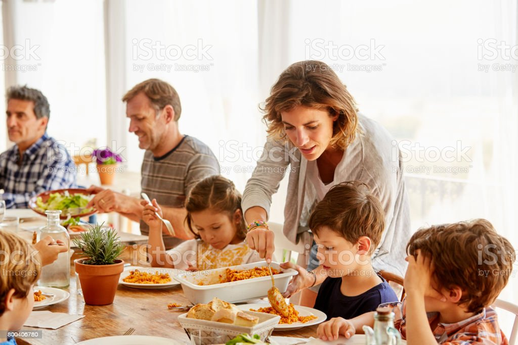 Mother serving food to children against window Mother serving food to children at table. Family is enjoying meal. They are sitting against window. 10-11 Years Stock Photo