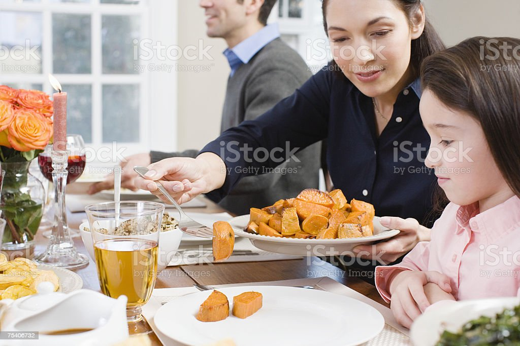 Mother serving sweet potatoes to daughter royalty-free stock photo