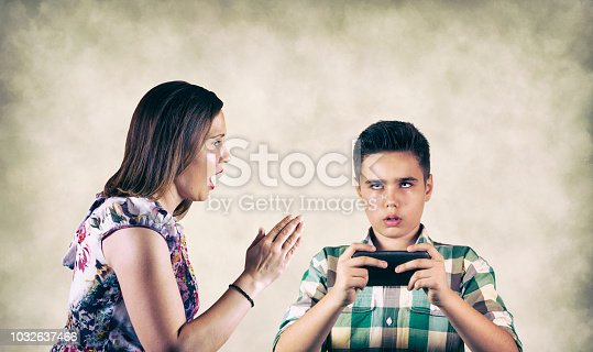 istock Mother shouting on son who plays mobile game 1032637466