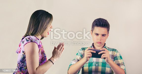 istock Mother shouting on son who plays mobile game 1036027364