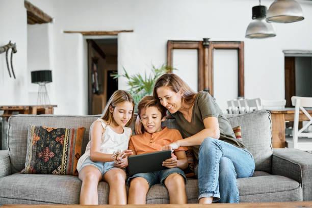 Mutter zeigt Kindern zu Hause digitales Tablet – Foto