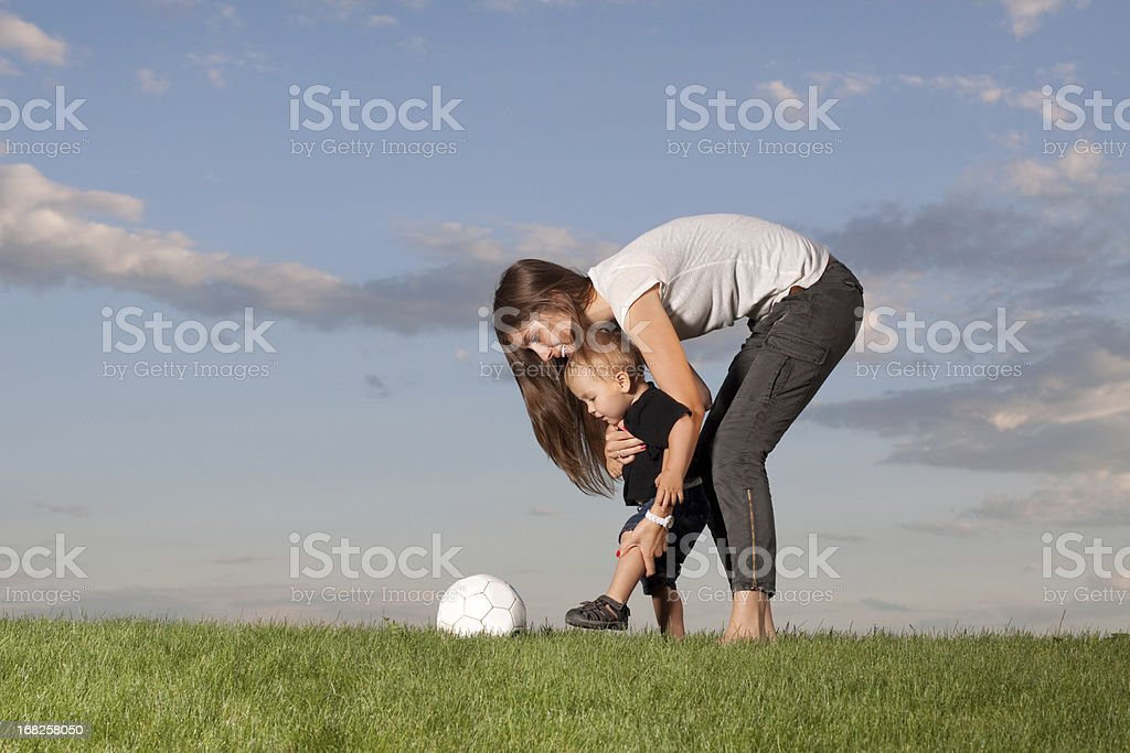 Mother showing her son how to kick a ball stock photo