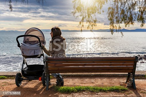Mother sits on a bench in a park by the sea with her baby in a stroller and enjoys the sunset