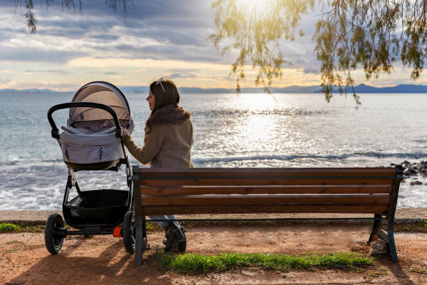 Mother sits on a bench with her baby in a stroller by the sea Mother sits on a bench in a park by the sea with her baby in a stroller and enjoys the sunset baby carriage stock pictures, royalty-free photos & images