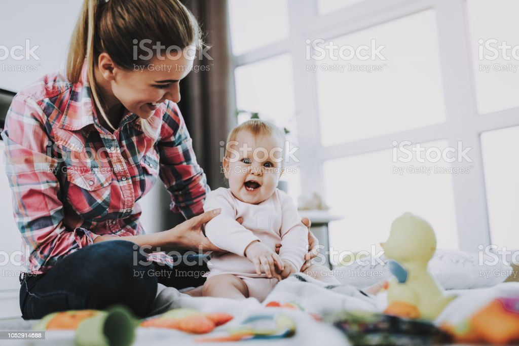 Mother Sits with Child on Floor and Holding Doll stock photo