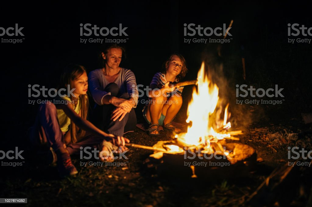 Mother with her daughter and son sitting next to the campfire at...