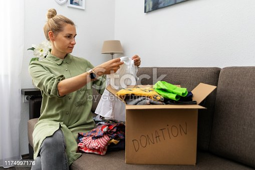 mother sitting on couch and sorting child clothes for donation