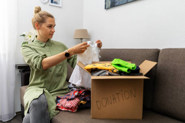 mother sitting on couch and sorting child clothes for donation stock photo