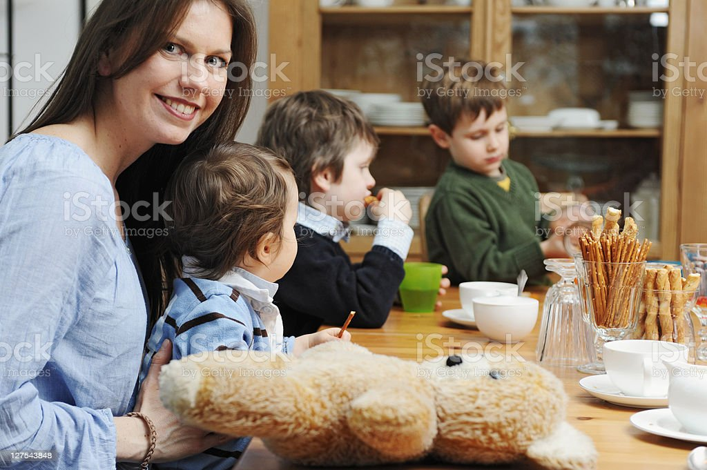 Mother sitting with sons at table stock photo