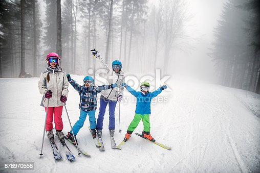 Mother skiing with kids on a misty winter day. Family is standing on ski slope and cheering at the camera.