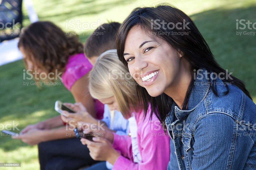 Mother smiling while her children play with phones royalty-free stock photo