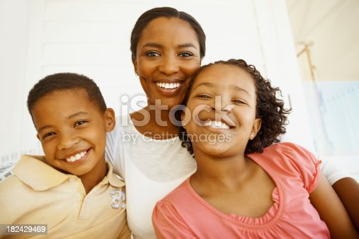 172407626istockphoto Mother smiling with son and daughter 182429469