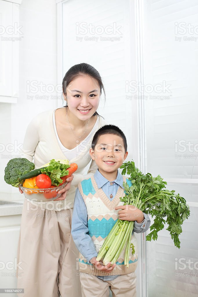 mother  son hold vegetables and fruits in the kitchen royalty-free stock photo