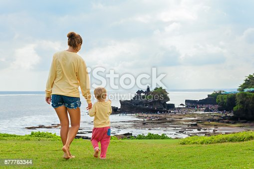 929671306 istock photo Mother, son look from cliff at Balinese temple Tanah lot. 877763344