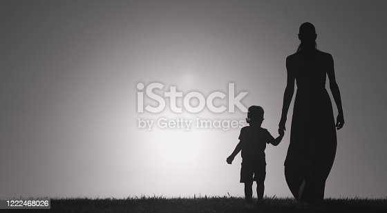 Mother and son walking together at sunset.