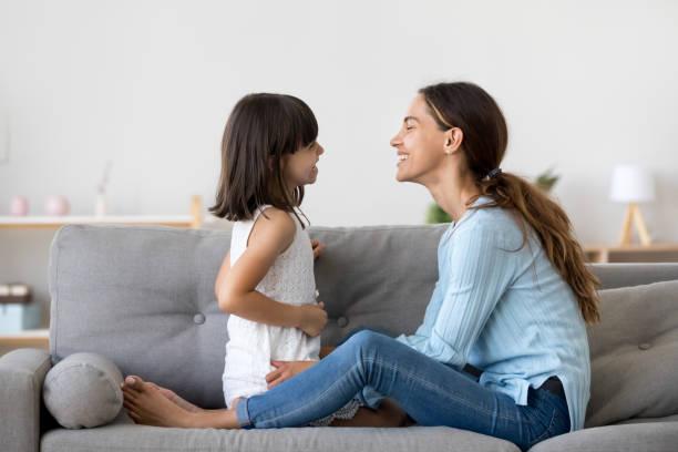 madre pasar tiempo con la pequeña hija hablando sentados en el sofá - hija fotografías e imágenes de stock