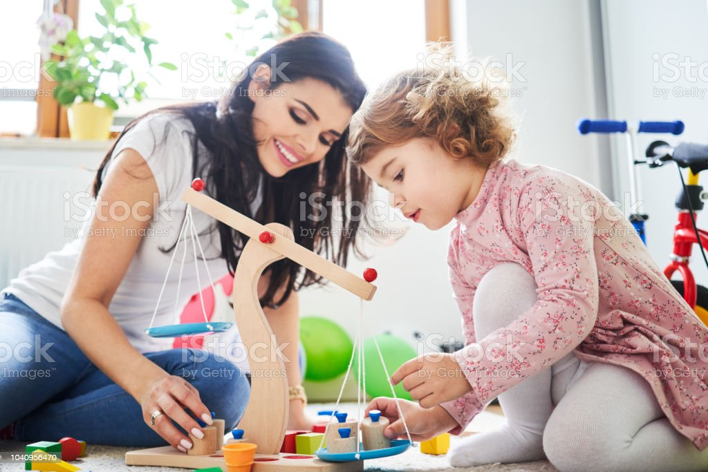 Mother spending time with her daughter playing with toys stock photo
