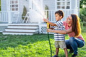 Mother splashing water and having fun with son on back yard