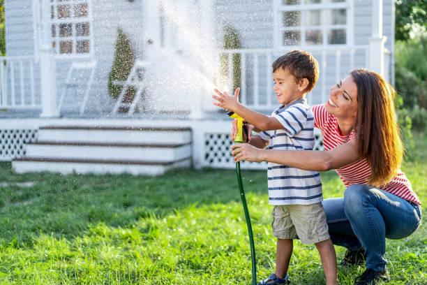mother splashing water and having fun with son on back yard - mãe criança brincar relva efeito de refração de luz imagens e fotografias de stock