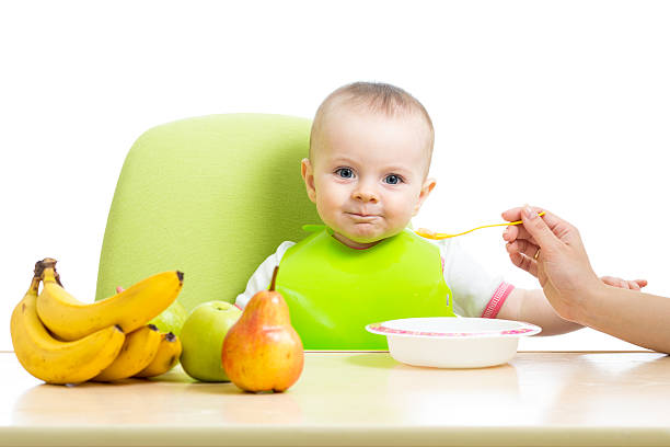 mother spoon feeding baby girl stock photo
