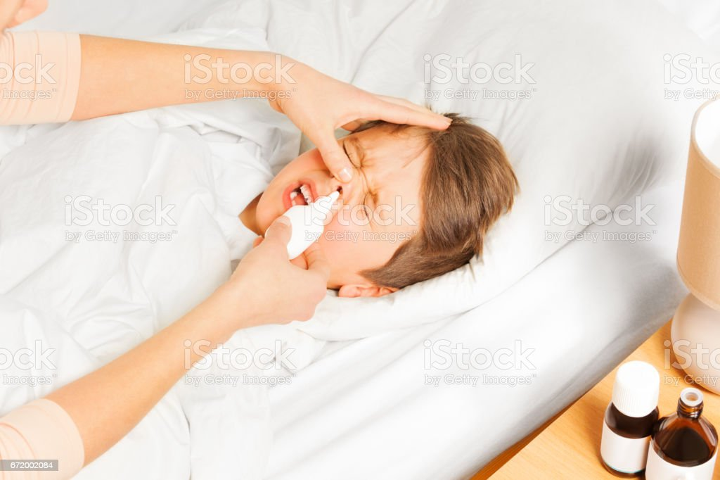Mother spraying her kid boy nasal spray in nose stock photo