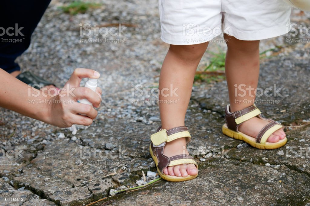 Mother spraying insect or mosquito repellents on skin girl, mosquito repellent for babies, toddlers that will protect your children from mosquitoes and other insects stock photo