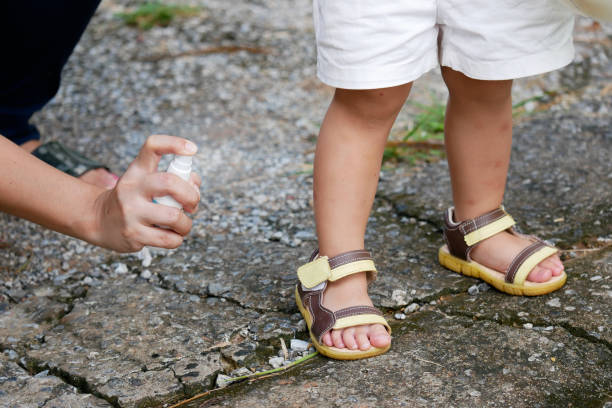 mother spraying insect or mosquito repellents on skin girl, mosquito repellent for babies, toddlers that will protect your children from mosquitoes and other insects - insect stock pictures, royalty-free photos & images