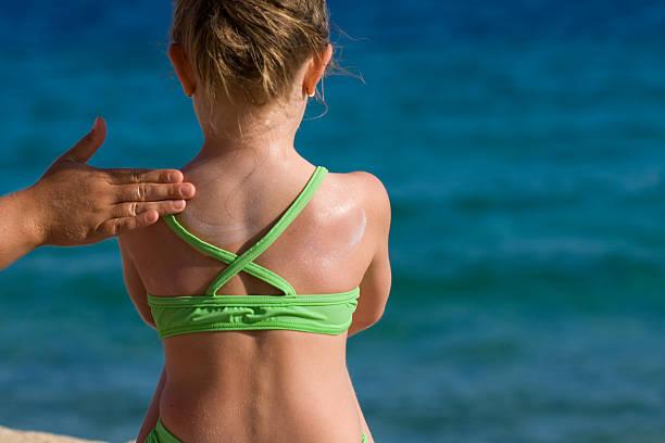 Mutter Aufstreichen Sonnencreme auf ihre Tochter Rückseite. – Foto