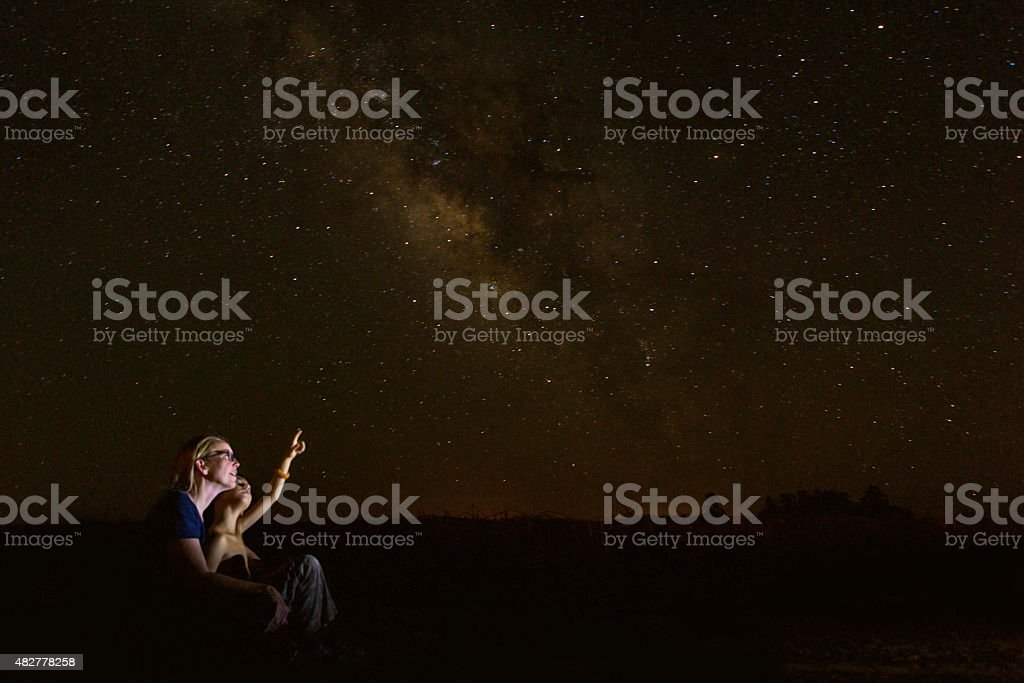 Mother star gazing with young son while he studies constellations stock photo